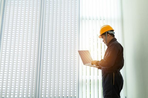 Engenheiro industrial em hard hat vestindo jaqueta de segurança usa touchscreen laptop.