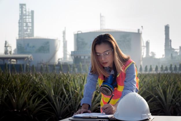 Engenheiro industrial feminino em um capacete de segurança trabalhando no site da refinaria de petróleo e usina, indústria, engenheiro e conceito de segurança.