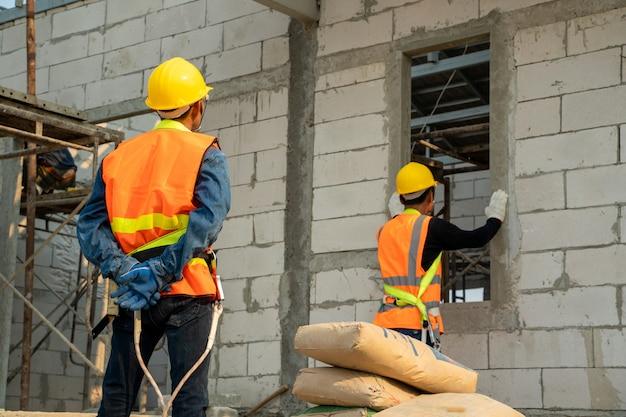 Engenheiro industrial trabalhando na construção de paredes exteriores com concreto leve e argamassa.