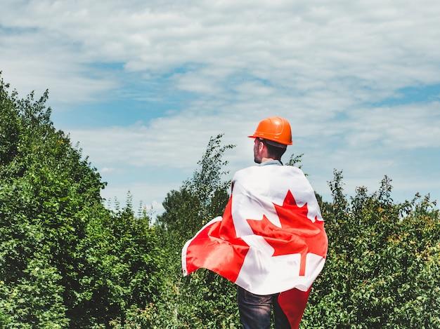 Engenheiro jovem, capacete de segurança laranja e bandeira canadense
