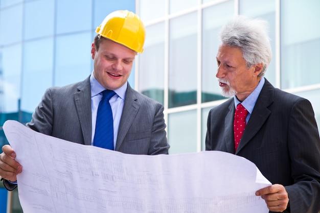 Engenheiro jovem mostrando algo para seu parceiro no canteiro de obras