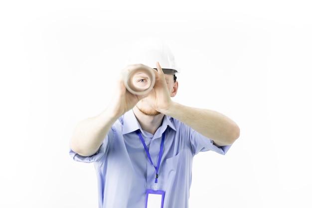 Engenheiro jovem positivo mantém desenho enrolado como luneta olha para a câmera