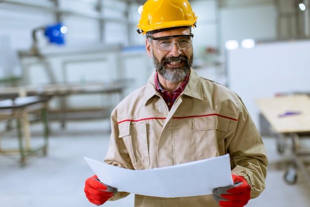 Engenheiro maduro bonito olhando plano na fábrica