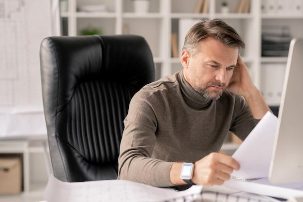 Engenheiro maduro com papéis olhando para um dos esboços enquanto os verifica pelo local de trabalho no escritório