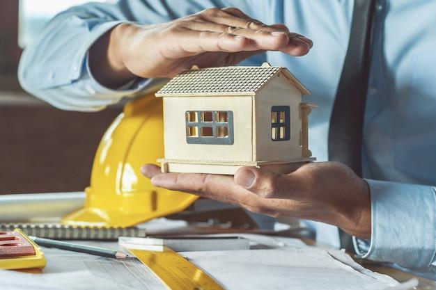 Engenheiro mão segurando modelo no local de trabalho. construção de conceito