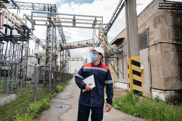 Engenheiro mascarado inspeciona uma subestação elétrica