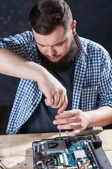 Engenheiro masculino desmontando laptop com chave de fenda