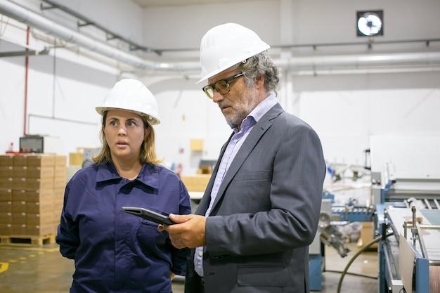Engenheiro masculino e operário feminino em capacetes em pé e falando no chão da fábrica, homem usando o tablet