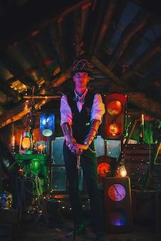 Engenheiro masculino em um terno steampunk, cartola, óculos com uma bengala na mão em uma oficina de relógio. conceito pós-apocalipse
