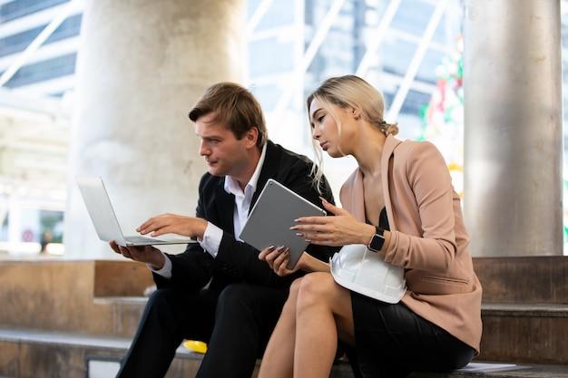 Engenheiro masculino with colleague que senta-se na escadaria e que olha no portátil contra a construção.