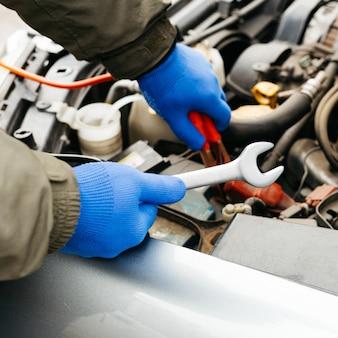 Engenheiro mecânico de automóveis usando uma chave inglesa no processo de consertar um carro