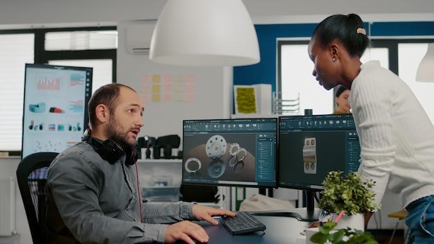 Engenheiro mecânico trabalhando em computador projetando em modelo cad de software d de motor enquanto co africano ...
