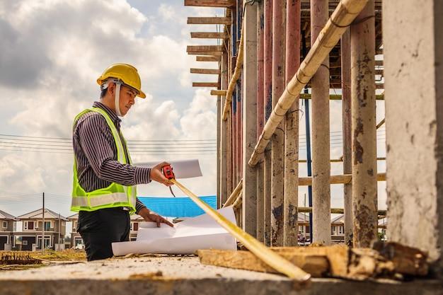 Engenheiro medindo piso de concreto no canteiro de obras