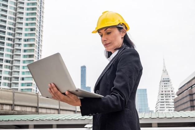 Engenheiro mulher, com, capacete amarelo, segurando, laptop, ligado, urbano