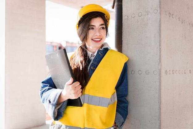 Engenheiro mulher no capacete e colete com uma prancheta nas mãos