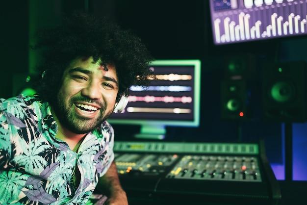 Engenheiro musical trabalhando dentro do estúdio de produção - foco no rosto do homem