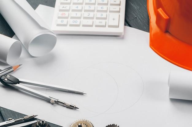 Engenheiro no local de trabalho com plantas, bússola, lápis e capacete de segurança