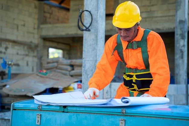 Engenheiro no trabalho com plantas na frente de um canteiro de obras