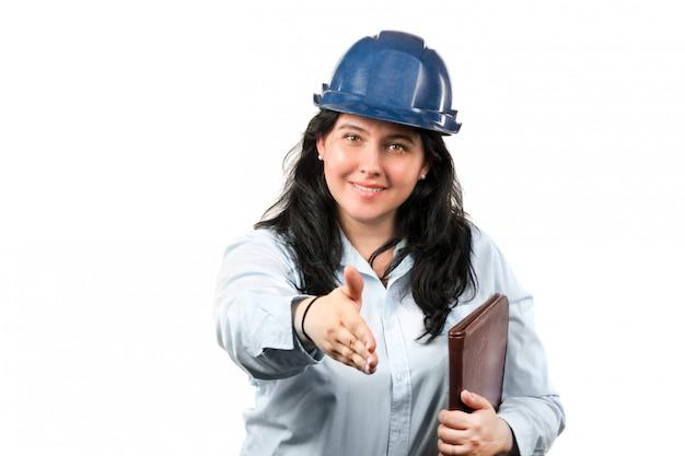 Engenheiro ou arquiteto moreno atrativo novo da mulher com o chapéu de segurança azul que puxa a mão para o aperto de mão isolado no branco