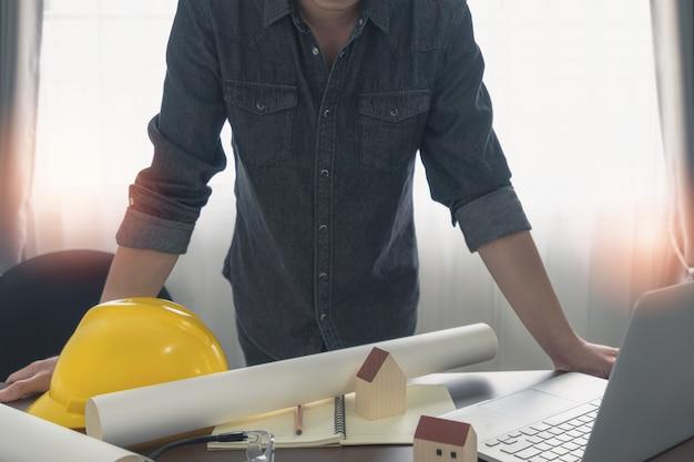 Engenheiro ou arquiteto olhando para a planta da construção e um notebook na mesa do escritório.