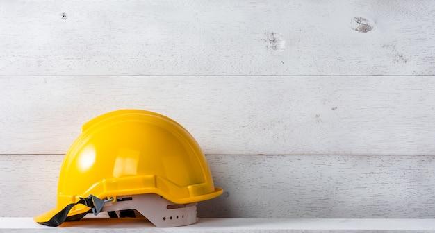 Engenheiro ou capacete de segurança do capataz na prateleira de madeira