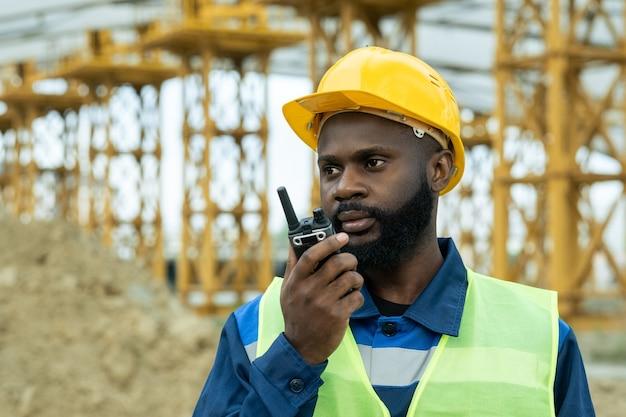 Engenheiro ou capataz de etnia africana usando walkie-talkie