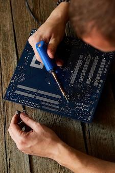 Engenheiro ou técnico repara placa de circuito eletrônico com ferro de soldar.