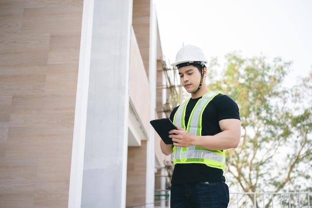 Engenheiro ou trabalhador da construção civil com capacete de proteção trabalhando no canteiro de obras