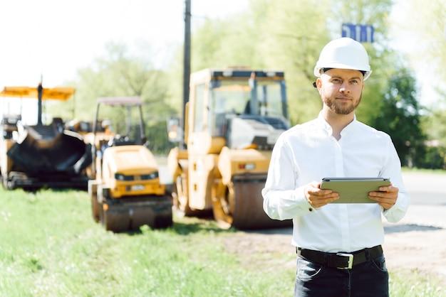 Engenheiro perto de máquinas rodoviárias. o conceito de construção de uma nova estrada de asfalto. reparação de estradas. trabalhador de serviço rodoviário perto da pista.