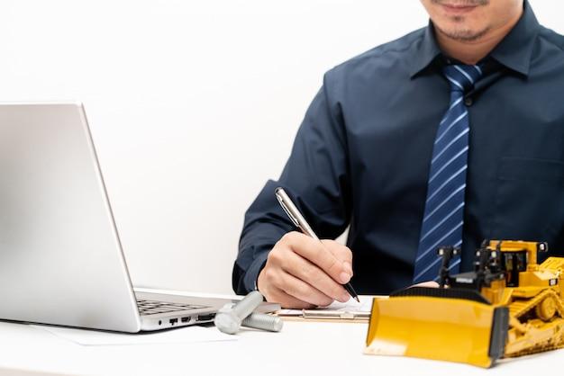 Engenheiro profissional escrevendo relatórios e durante o dia de trabalho no escritório, conceito de máquinas pesadas de manutenção de reparação