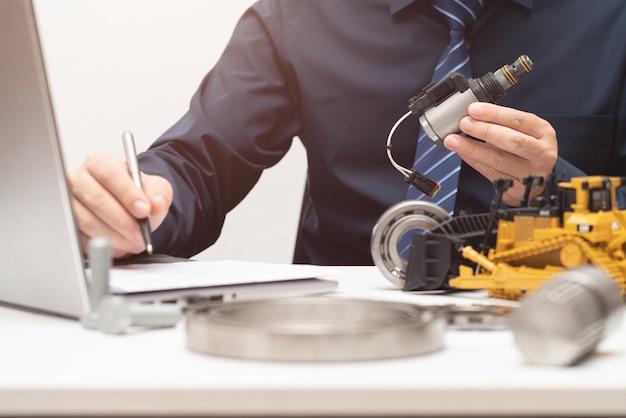 Engenheiro profissional inspeciona válvula solenóide e redige relatórios para durante o dia de trabalho no escritório; conceito de maquinaria pesada de manutenção de reparação