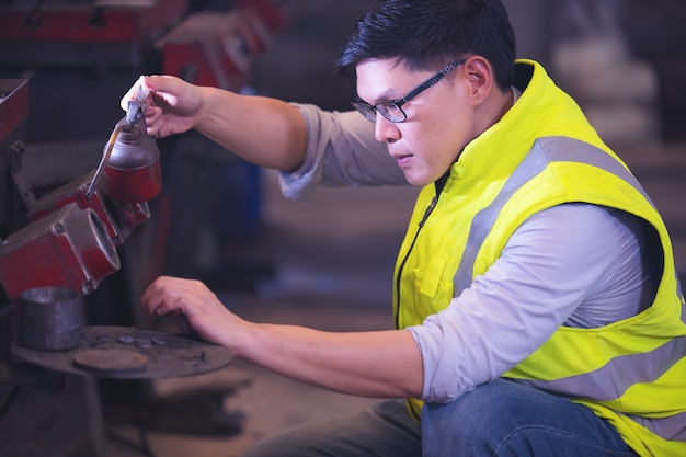 Engenheiro profissional metalúrgico operando centro de máquina na oficina de fabricação, verifique a configuração do sistema de segurança de fato