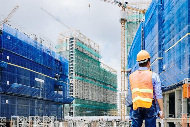 Engenheiro profissional olhando para um prédio em construção