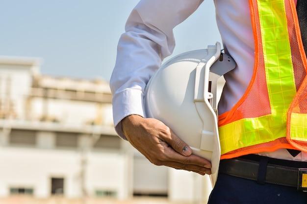 Engenheiro profissional segurando capacete branco no fundo da construção do local