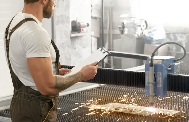 Engenheiro que controla o corte a laser de plasma de metal.