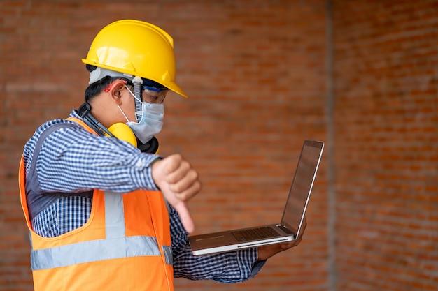 Engenheiro que não apresenta um bom símbolo manualmente com a profissão infeliz do trabalho devido à situação da doença de covid-19.