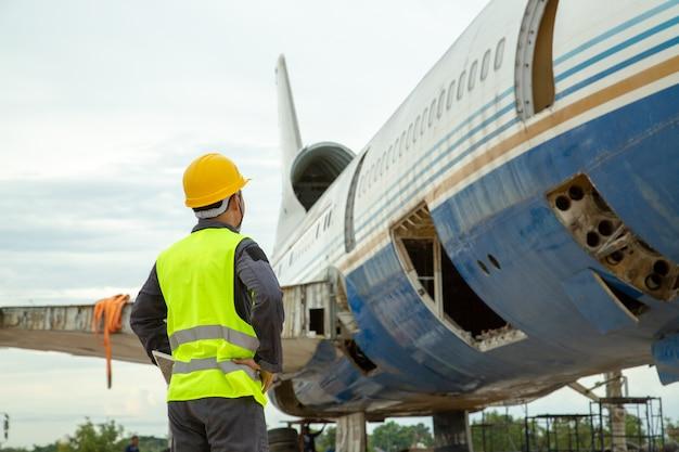 Engenheiro que olha o avião velho para a manutenção que um avião está executando reparos.