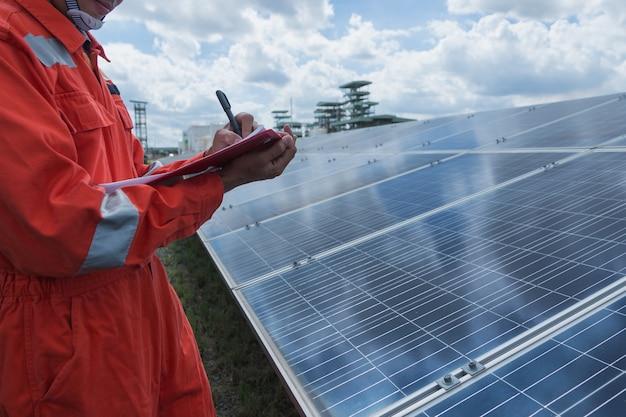 Engenheiro que trabalha na verificação e manutenção de equipamentos elétricos na usina solar; engenheiro que verifica o painel solar em operação rotineira na usina solar