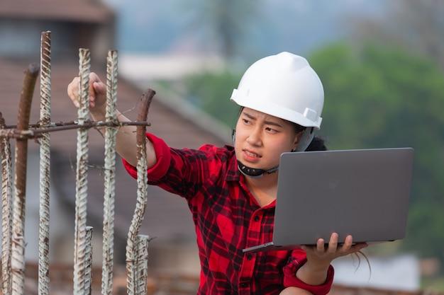 Engenheiro segurando laptop verifique o trabalho de construção, o conceito do dia do trabalho