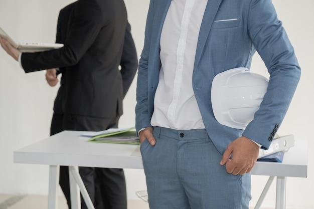 Engenheiro segurando o capacete branco e pé na frente de sua equipe no escritório.