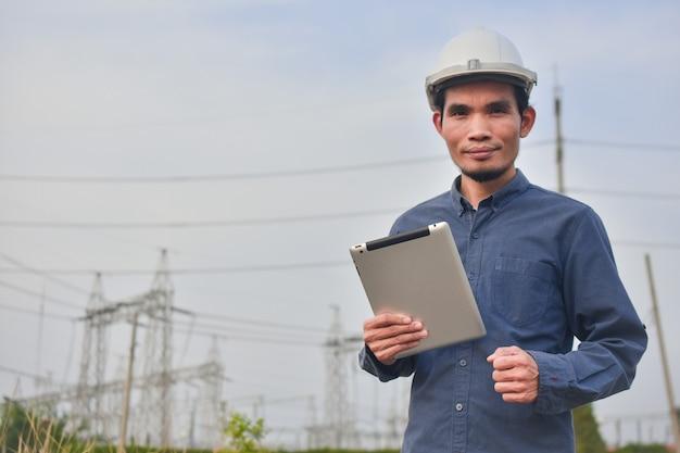 Engenheiro segurando o fundo do sistema de alta tensão ao ar livre do tablet