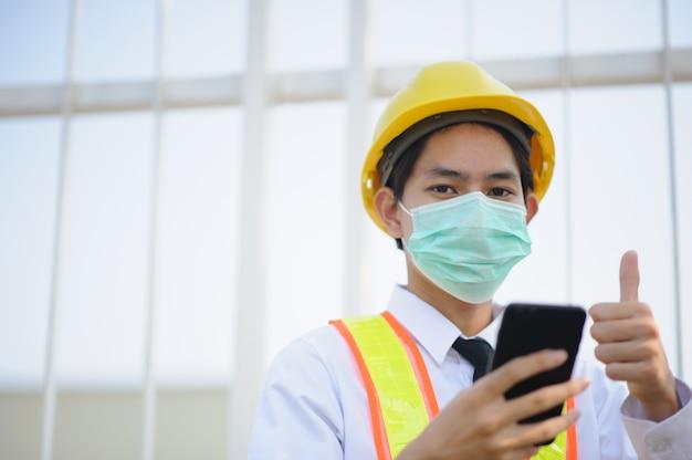 Engenheiro, segurando o telefone móvel esperto usar máscara médica trabalhar no canteiro de obras