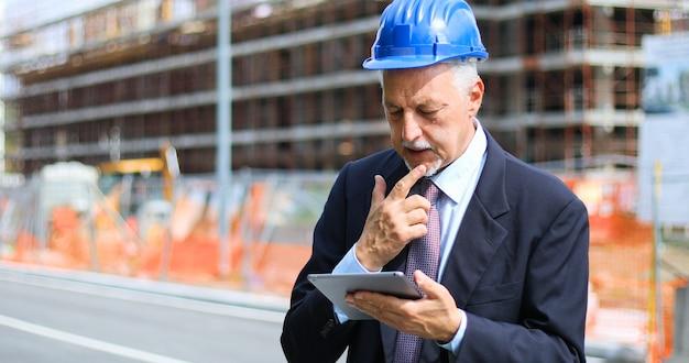 Engenheiro sênior homem de terno e capacete trabalhando no tablet pc
