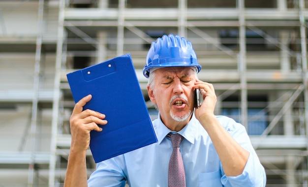 Engenheiro sênior irritado, gritando com o telefone