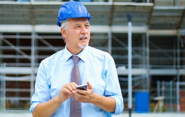 Engenheiro sênior, usando seu smartphone ao ar livre em um canteiro de obras