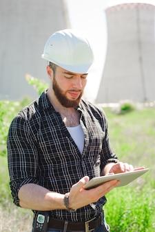 Engenheiro sorridente usando um tablet em uma instalação.