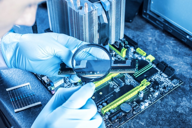 Engenheiro técnico computadores em luvas nas mãos está analisando a falha.