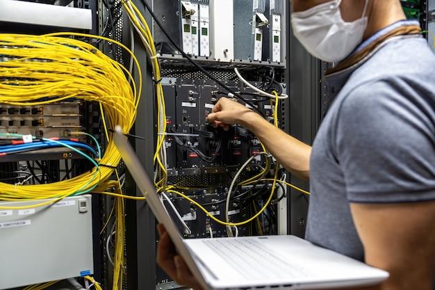 Engenheiro técnico corrigindo problema com servidores e dados na sala de cabos