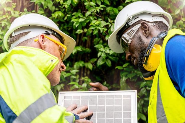 Engenheiro, técnico de fábrica, homens verificando se há tecnologia sustentável no painel de células solares