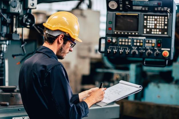 Engenheiro técnico de profissão jovem operar máquina pesada para cnc automatizado na fábrica, trabalhador com lista de verificação.
